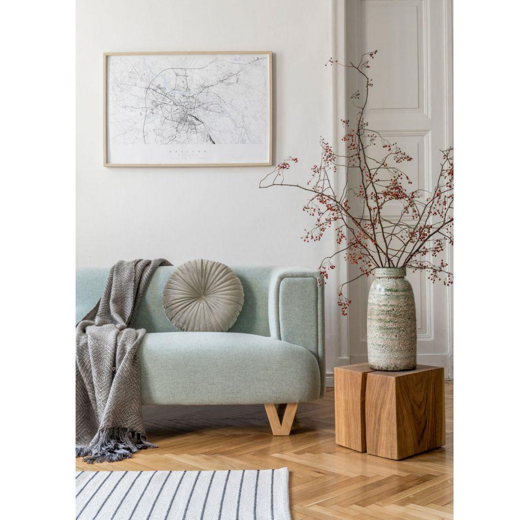 obývačka v prírodnom štýle zariadená pohovkou v mätovo sivej, dreveným stolíkom s keramickou vázou v zelených odtieňoch a pásikavým kobercom