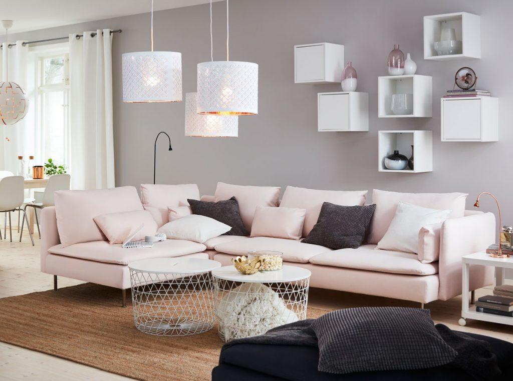 obývacia izba v severskom štýle s bielymi svietidlami, ružovou sedačkou, okrúhlymi drôtenými stolíkmi a štvorcovými bielymi policami