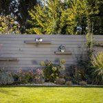 Malá záhrada oplotená WPC doskami, pri ktorých sú trvalkové záhony.