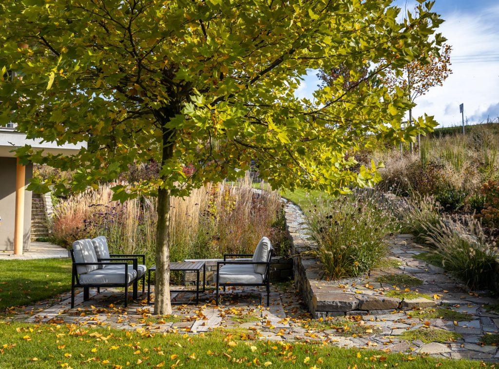 Prírodná záhrada s terasou z andezitových platní a dubových fošní, na ktorej je umiestnené sedenie pod platanom