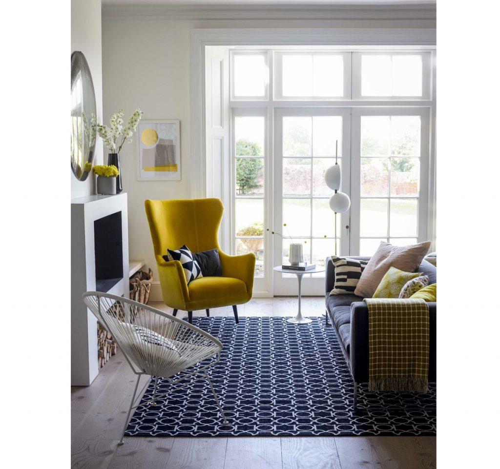Interiérové trendy 2020: obývačka zariadená v kombinácii rôznych vzorov, s modrým gaučom, vzorovaným kobercom, žltým ušiakom a vzorovanými vankúšmi.