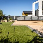 Moderný rodinný dom s malou záhradou so stupňovitou terasou s krytým bazénom, trávnatou plochou, záhradným domčekom a vyvýšenými zeleninovými záhonmi.