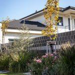 Malá záhrada s trvalkovými záhonmi z ruží a okrasných tráv a s okrasnou hruškou.