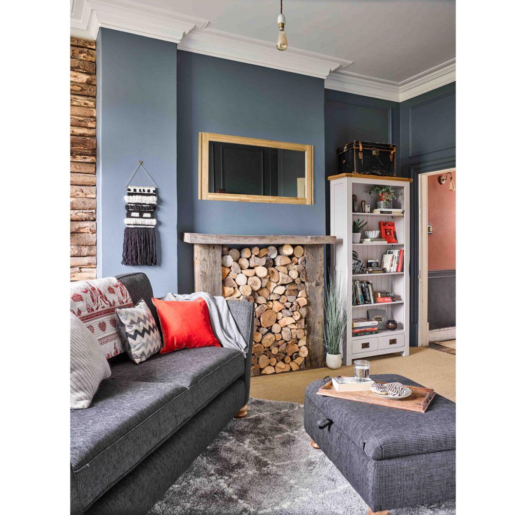ako znížiť náklady na dodávku tepla: interiér so sivou pohovkou, dreveným nábytkom a priestorom na uskladnenie dreva