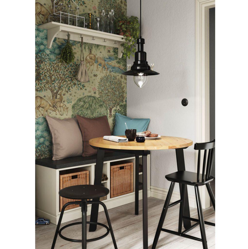 Jedálenský kút v malom priestore s lavicou s úložnými priestormi, okrúhlym stolom, stoličkami, farebnou tapetou s prírodným motívom a otvorenou poličkou.