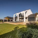 Moderný rodinný dom s malou elegantnou záhradou s trávnatou plochou, stupňovitou terasou s bazénom, trvalkovými záhonmi, vyvýšenými záhonmi so zeleninou a ovocnými stromami.