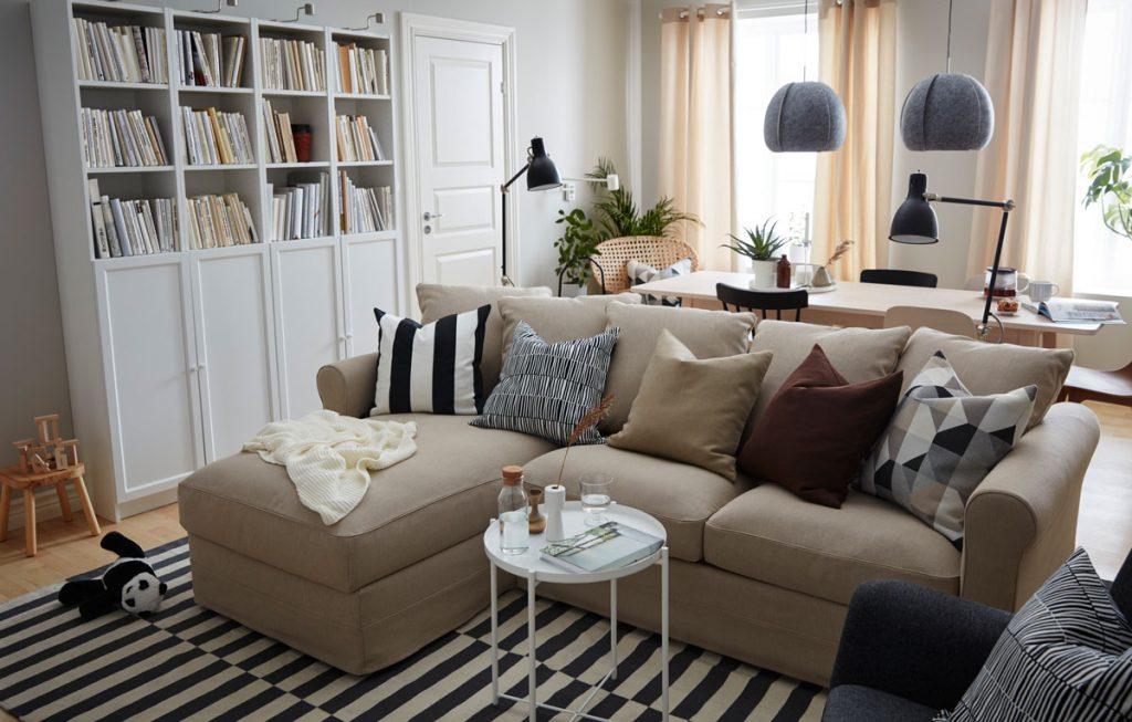 Spojenie obývačky s jedálňou v malom byte, s knižnicou, svetlohnedou pohovkou, stolíkom, čiernobielym kobercom a jedálenským stolom.