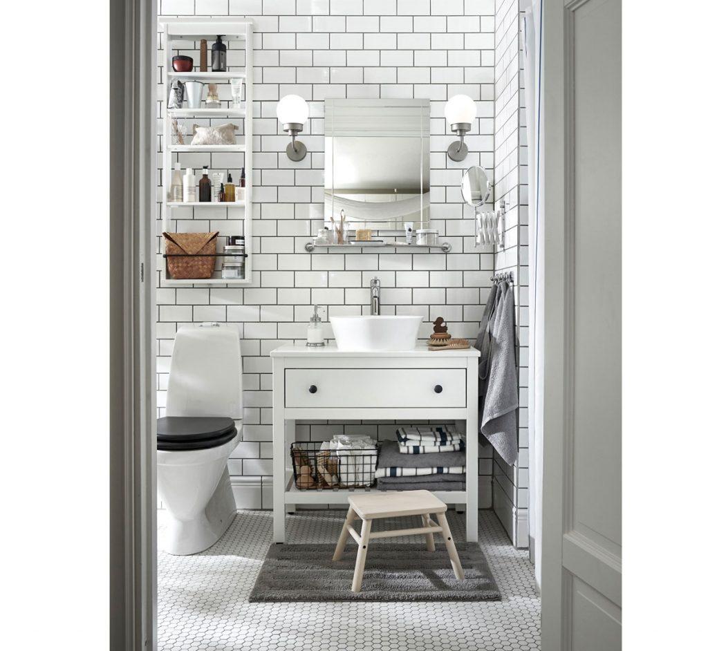 Malá kúpeľňa s bielym lesklým obkladom, bielou otvorenou skrinkou na úmyvadlo a závesnou otvorenou policou.