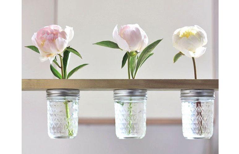 polička s vázami na kvety vyrobená zo zrecyklovanej drevenej dosky a sklenených zaváraninových pohárov s vrchnákom na závit