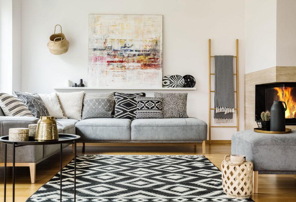 Interiérové trendy 2020: obývačka so sivou sedačkou, čiernym kovovým stolíkom, textíliami a doplnkami s geometrickými vzormi a dekoráciami z prírodných materiálov.