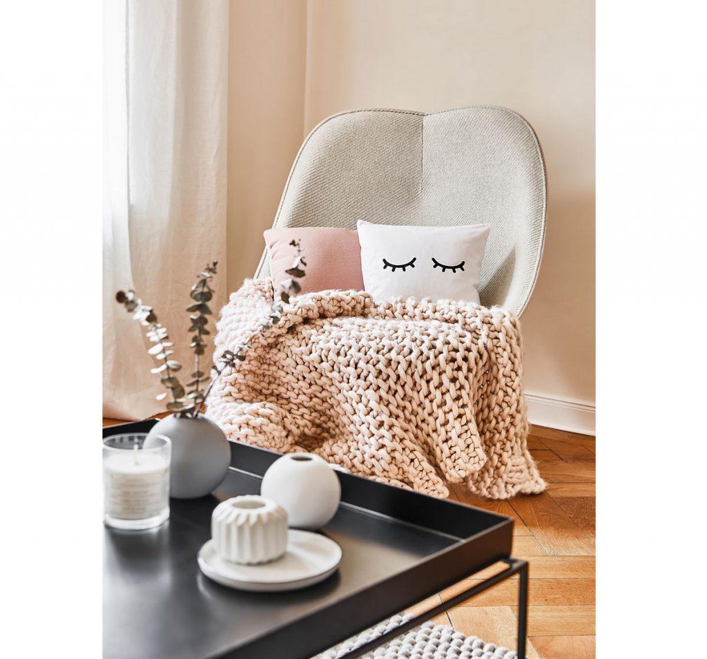 Interiér zariadený v odtieňoch perlovej farby, s krémovým čalúneným kreslom, čiernym stolíkom, bielymi dekoráciami a textíliami vo farbách bielej a ružovej.