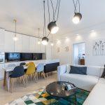 Moderný priestor, v ktorom je spojená kuchyňa s obývačkou. Kuchyňa s bielou kuchynskou linkou, s ostrovčekom súvisle vedúcim do jedálenského stola s čalúnenými stoličkami. Obývačka s bielou sedačkou tvaru L a farebným geometrickým kobercom.