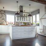 Kuchyňa v drevodome s ručne vyrobenou bielou drevenou kuchynskou linkou, ostrovčekom a hojdačkou.