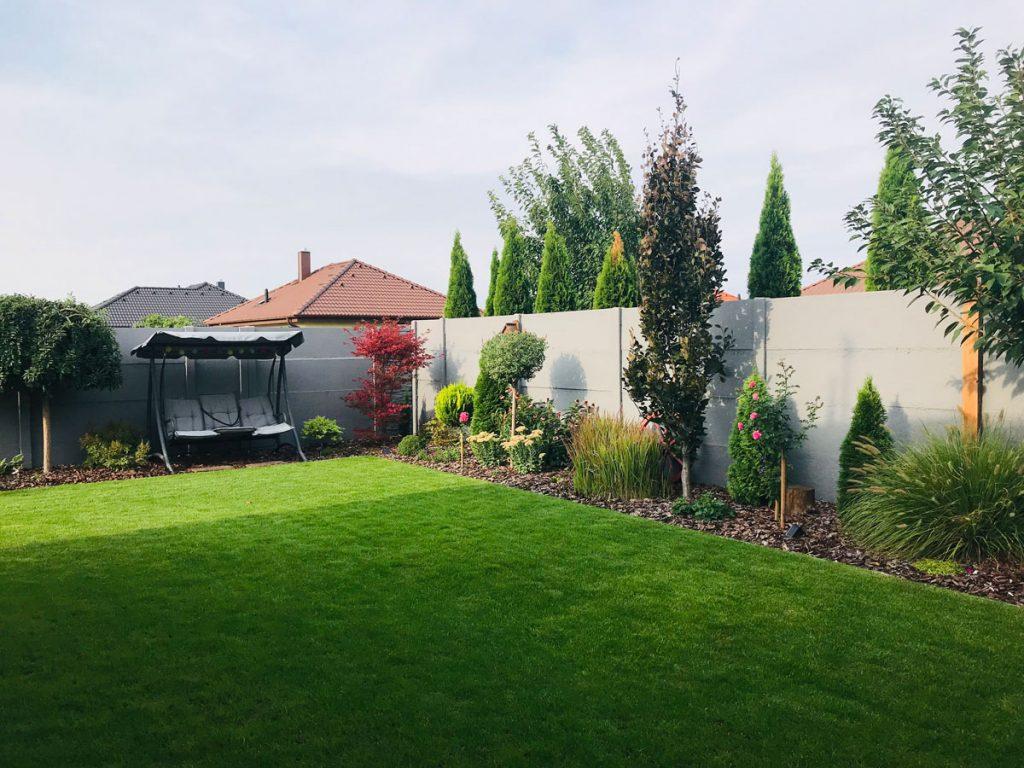 Svojpomocne vybudovaná záhrada s trvalkovými záhonmi, ihličnanmi, trávnikom a hojdačkou.