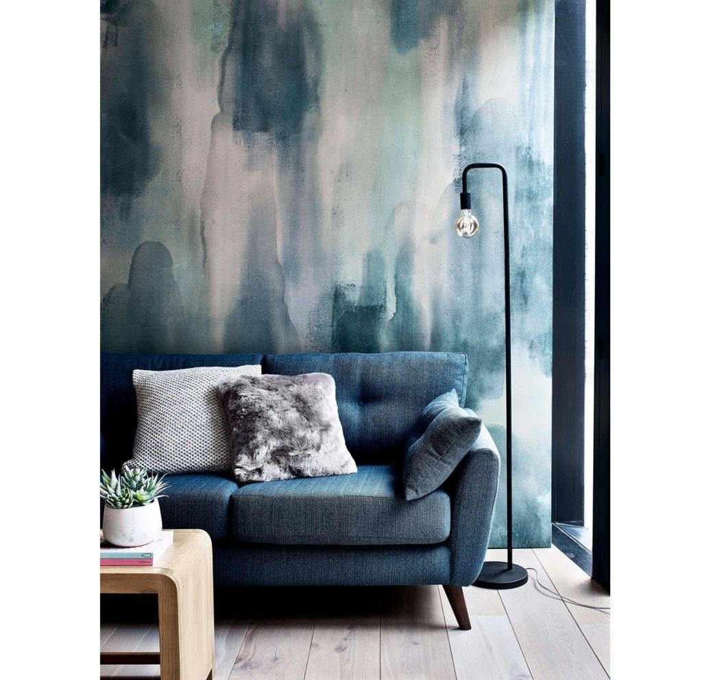 Ako upraviť steny v obývačke: interiér s akvarelovou stenou a modrou pohovkou.