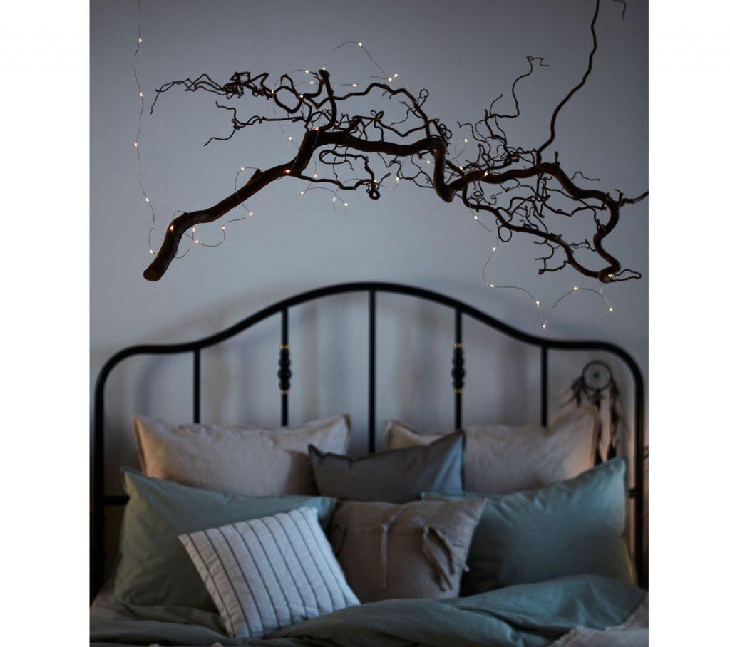 Spálňa so svetelnou reťazou aranžovanou na konári, ktorý visí nad posteľou.