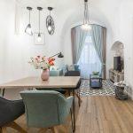 Zrekonštruovaný starý byt v pastelových farbách, s retro čalúnenými jedálenskými stoličkami, dreveným stolom a obývacou časťou s pohovkou a TV umiestnenou v klenbovom výklenku s tehlovou stenou.