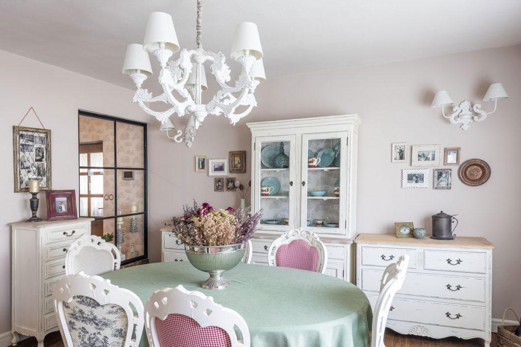 Vidiecka kuchyňa s bielymi komodami, bielym príborníkom, okrúhlym jedálenským stolom a bielymi zdobenými stoličkami.