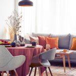 Obývačka a jedáleň v jednom, s pohovkou, okrúhlym stolom a čalúnenými retro stoličkami, prepojená farebne oranžovou, červenou a sivou.