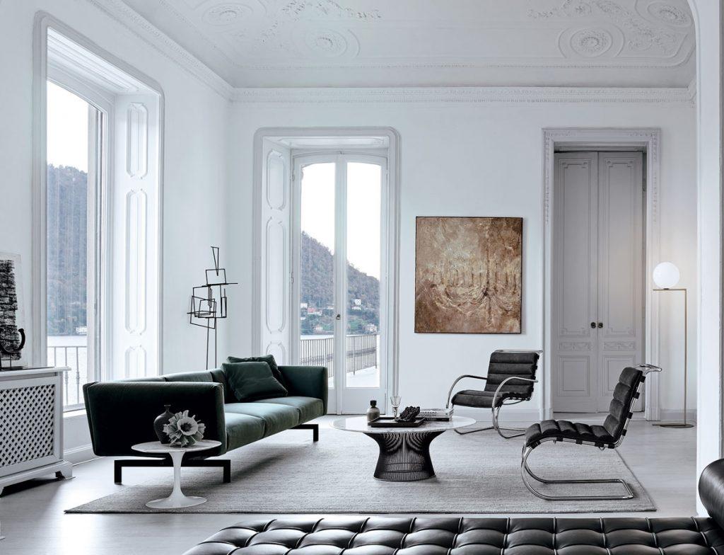 Elegantný retro interiér vo farbách čiernej a sivej, s pohovkou, okrúhlym stolíkom, stoličkami na esovitej konštrukcii.