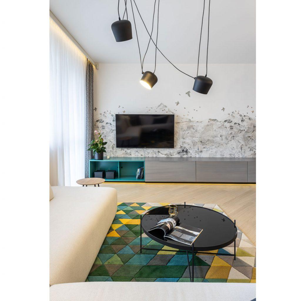 Moderná obývačka s farebným kobercom, okrúhlym skleneným stolíkom, s nízkymi úložnými skrinkami popri stene a tapetou s prírodným motívom.
