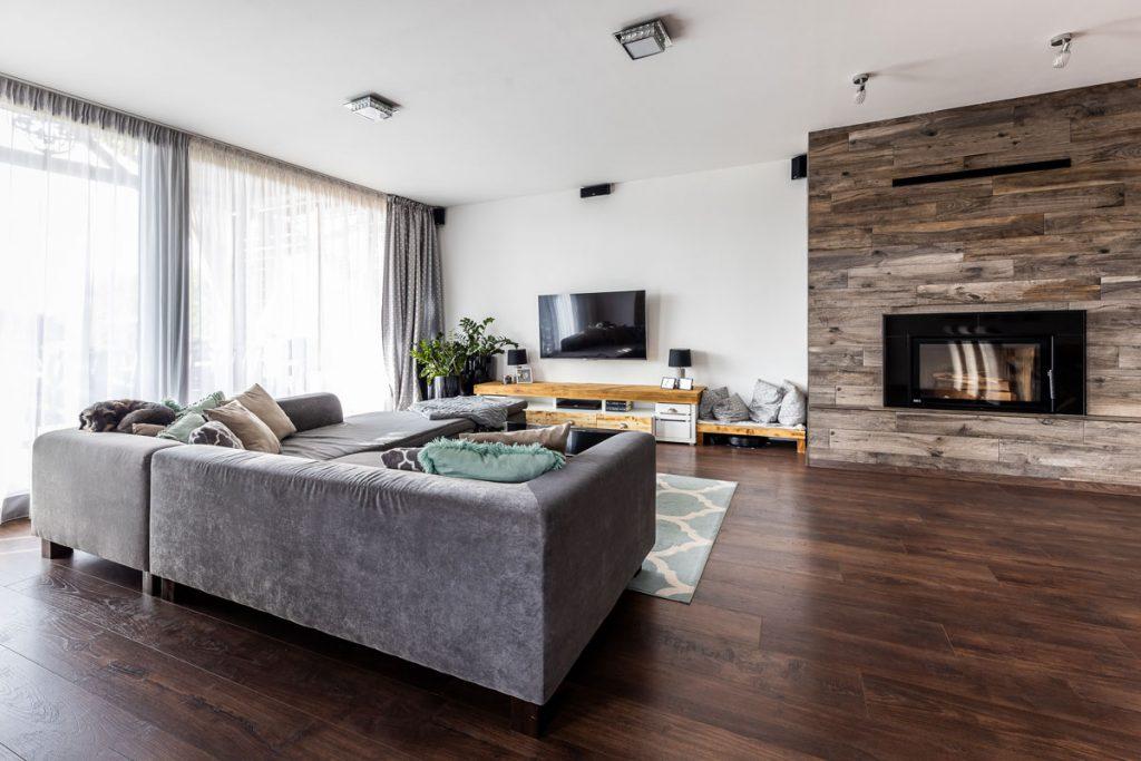 Obývačka v modernom vidieckom štýle so sivou sedačkou v tvare L a obloženým krbom.