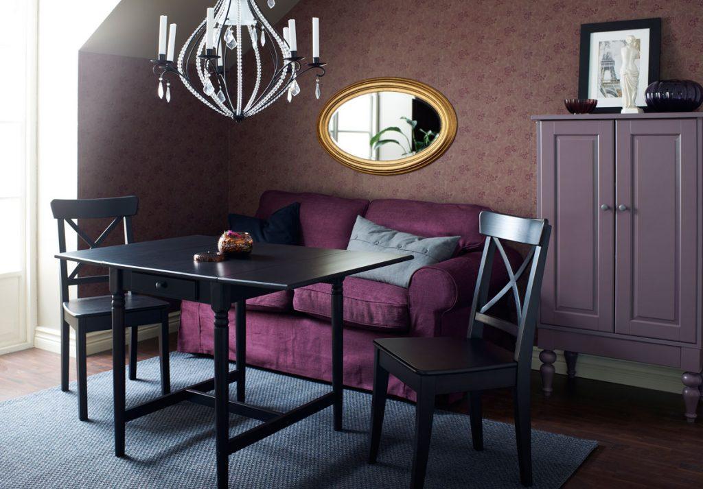 Obývačka a jedáleň v jednom, s fialovou pohovkou dreveným stolom a drevenými stoličkami.