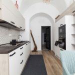 Kuchyňa v menšom starom byte s klenbami, bielou kuchynskou linkou, otvorenými policami a vstavanými spotrebičmi.