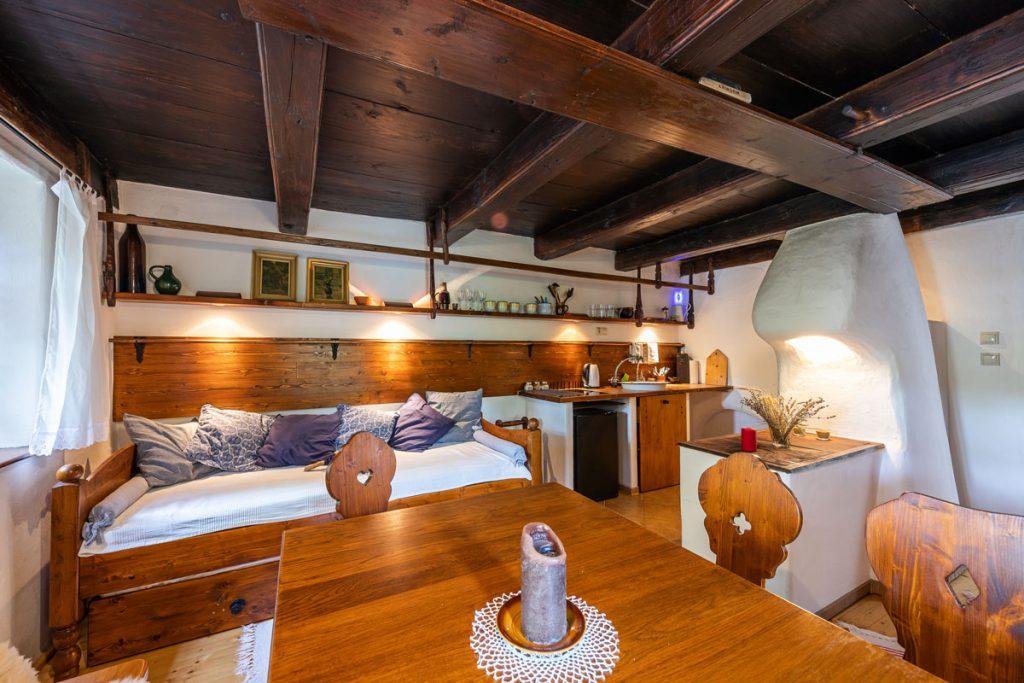 Interiér tradičnej chalupy s dreveným stropom, drevenou váľandou, jednoduchým drezom a sporákom, jedálenským stolom a murovanou pieckou.