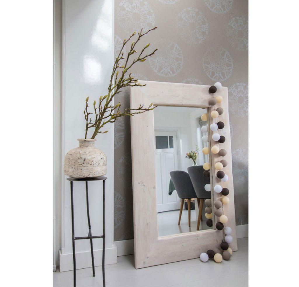 Svetelná reťaz aranžovaná na mohutnom zrkadle, ktoré je opreté o stenu.