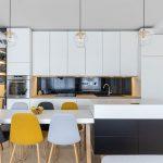 Kuchyňa s jedálňou so sivou kuchynskou zostavou prechádzajúcou do knižnice v chodbe, s jedálenským stolom prepojeným s ostrovčekom a čalúnenými stoličkami.