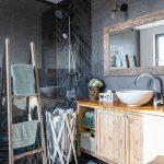 Kúpeľňa s tmavým obkladom, sprchovacím kútom, dreveným rebríkom na uteráky, dreveným košom na prádlo a drevenou skrinkou s umývadlom.