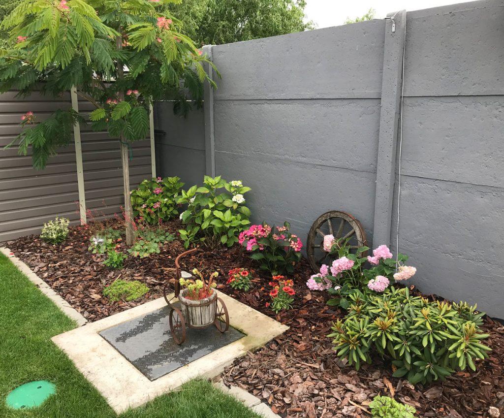 Svojpomocne vybudovaná záhrada s trvalkami a dekoráciami.