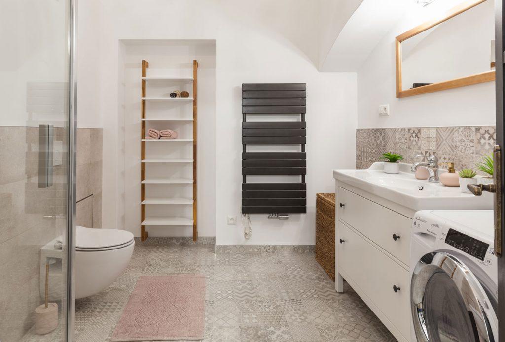Kúpeľňa s klenbami, so vzorovanými kachličkami, WC, sprchovým kútom, práčkou, umývadlom so skrinkou a otvorenými policami na uteráky.