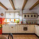 Smotanová kuchynská linka v rustikálnom štýle so vzorovanými kachličkami, retro červenou chladničkou a ozdobnými stropnými trámami.