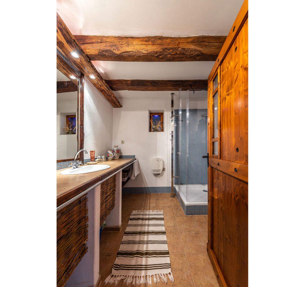 Kúpeľňa v tradičnej chalupe s masívnymi drevenými dverami, stropnými trámami, sprchovacím kútom a umývadlom vsadeným do dosky.