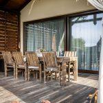Drevodom s drevenou terasou a dreveným jedálenským stolom a stoličkami.