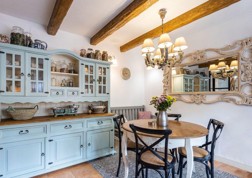 Vidiecka kuchyňa s modrým kredencom, okrúhlym kuchynským stolom, zdobeným lustrom a zdobeným veľkým zrkadlom.