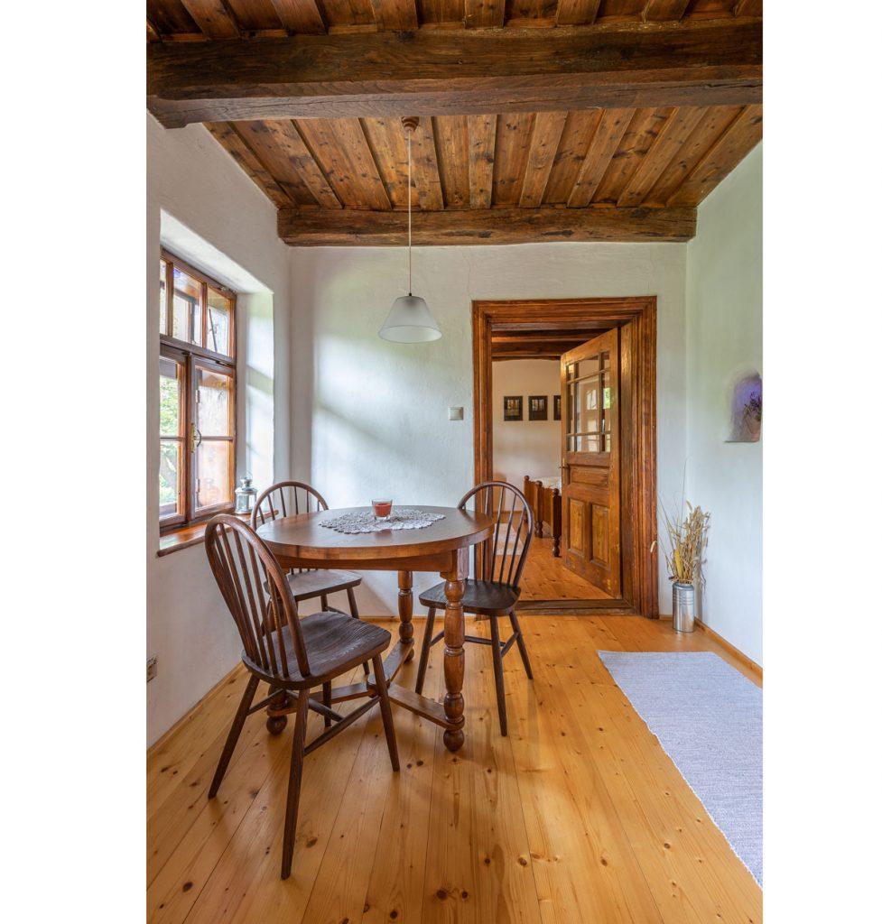 Interiér zrekonštruovanej tradičnej chalupy s masívnym dreveným stropom, okrúhlym starodávnym jedálenským stolom a stoličkami.