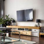 Obývačka s drevenými policami pod závesnou TV, so vzorovaným kobercom a stolíkom z kovu a skla.
