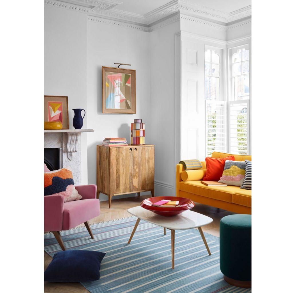 Retro interiér s ružovým kreslom a žltou pohovkou, zelenou taburetkou, drevenou skrinkou a farebnými textíliami.