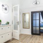 Predsieň s bielym botníkom, čiernymi dvojkrídlovými dverami a dizajnovými svietidlami v tvare ventilátora.