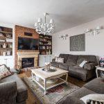 Obývačka v rustikálnom štýle s troma pohovkami, zdobeným stolíkom, knižnicou, komodami a krbom obloženým tehlou.