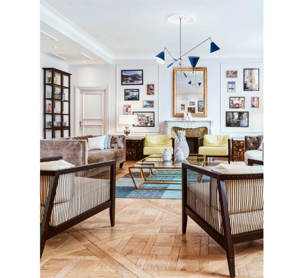 Interiér v retro štýle s vypletanými kreslami, pohovkou, zlatým stolíkom, kozubom a trojramenným lustrom.