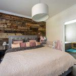 Spálňa v drevodome susediaca s kúpeľňou. V spálni je manželská posteľ, detská postieľka a stena s dreveným obkladom.
