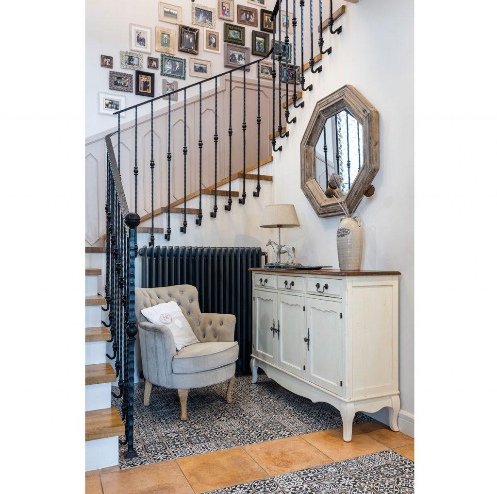 Interiér so schodiskom, pod ktorým je vidiecke kreslo s bielou komodou a zrkadlom.