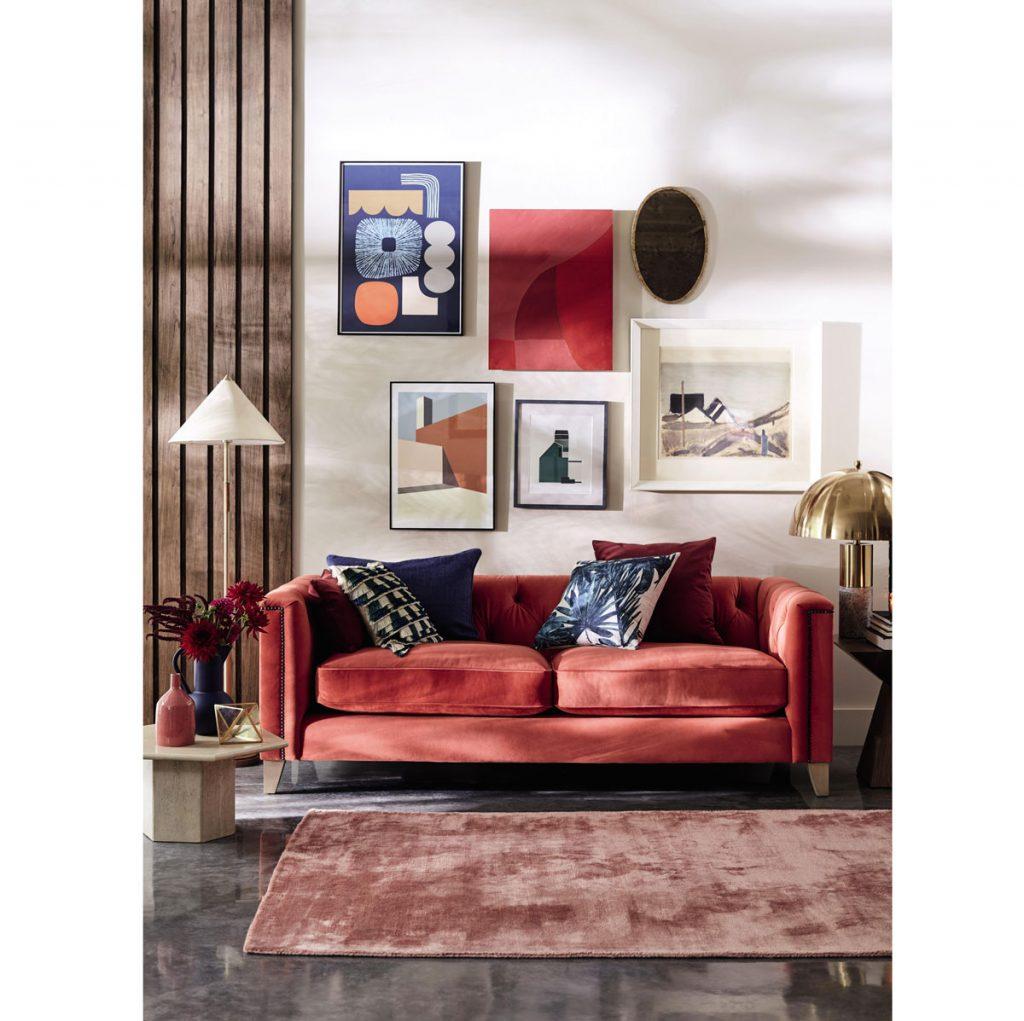 Úprava stien v obývačke: interiér s červenou zamatovou sedačkou a obrazmi na stenách farebne ladiacimi s nábytkom.