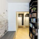 Moderný interiér chodby s čiernou knižnicou, ktorá ukončuje kuchynskú linku.