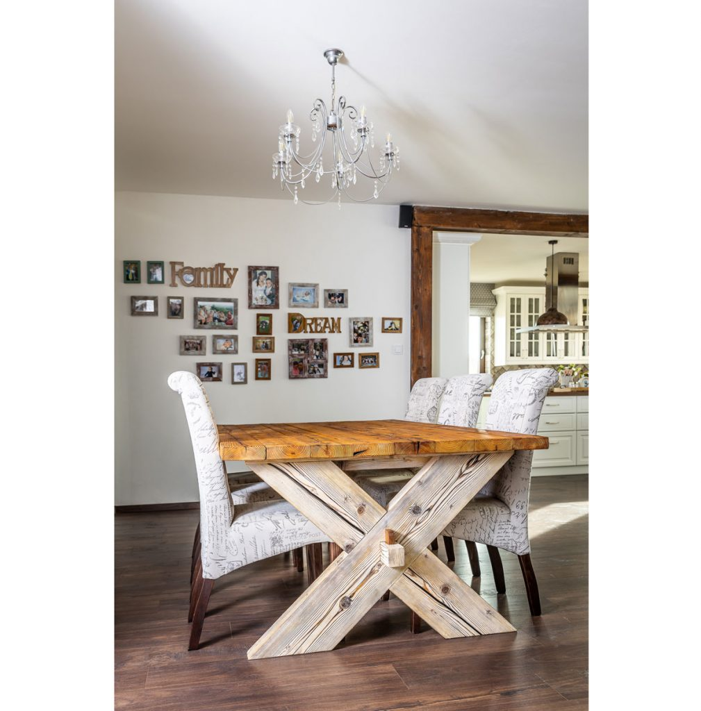Jedálenský kút so stolom z masívneho dreva a stoličkami v bielej farbe.
