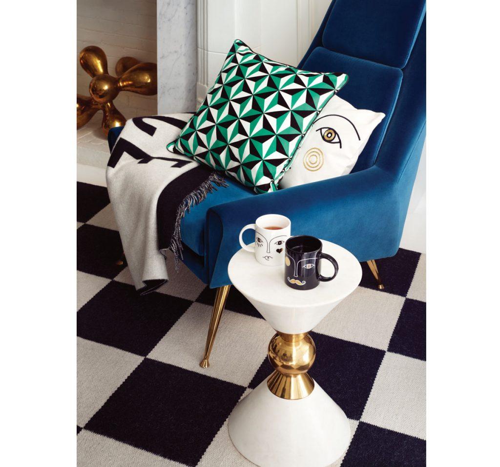 Zamatové modré kreslo s vankúšom s geometrickým vzorom a s motívom ľudskej tváre a stolík s motívom tváre na hrnčekoch.